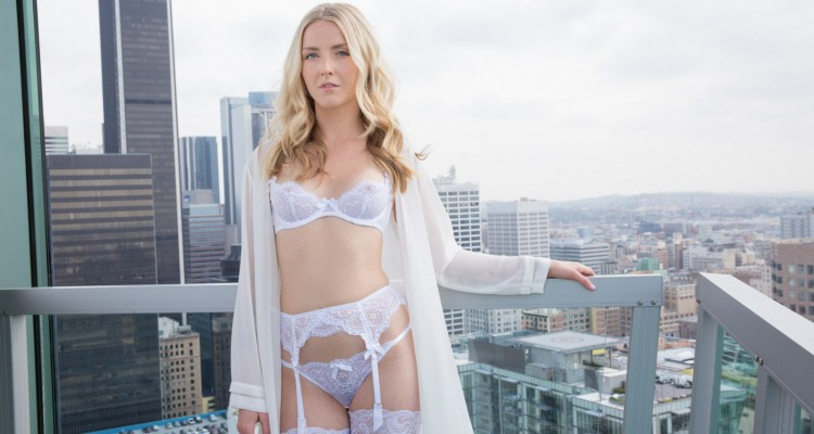 Karla Kush posing on a balcony in white lingerie