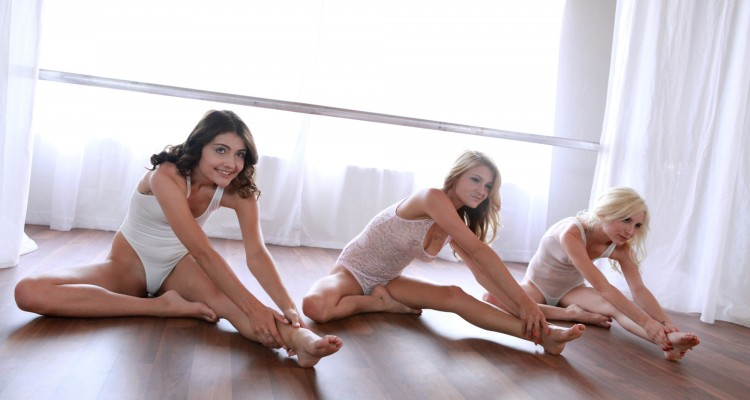three petite ballerinas stretch before class